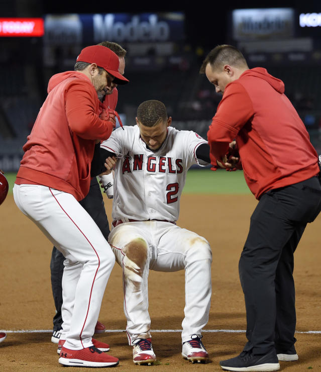 Los Angeles Angels' Andrelton Simmons, center, is helped up by manager Brad Ausmus, left, and a trainer after he was injured while being thrown out at first during the eighth inning of a baseball game against the Minnesota Twins Monday, May 20, 2019, in Anaheim, Calif. (AP Photo/Mark J. Terrill)