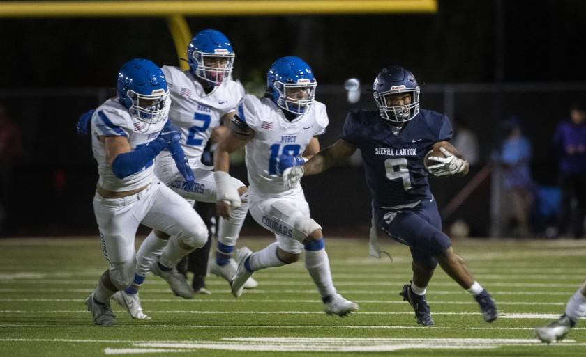 CALABASAS, CA - SEPTEMBER 24, 2021: Sierra Canyon running back Jason Jones (9) outruns Norco defenders Andrew Parker (25), Logan Grier (2), and Darius Ward (10) in the first half at Calabasas High School on September 24, 2021 in Calabasas, California.(Gina Ferazzi / Los Angeles Times)