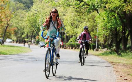 Woman flashes victory signs as she rides a bicycle during Girls on Bike rally in Islamabad