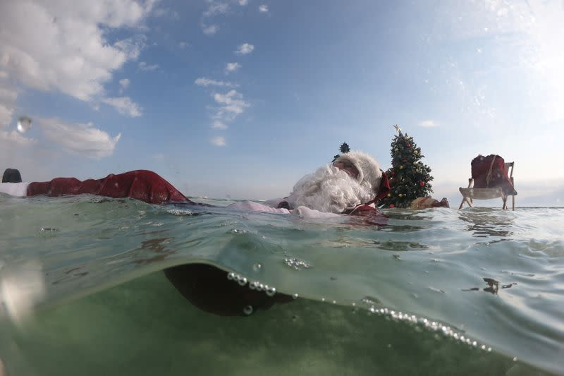 Issa Kassissieh, wearing a Santa Claus costume, floats in the Dead Sea near a Christmas tree placed on a salt formation, near Ein Bokeq