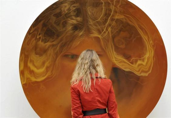 A visitor is reflected in a sculpture called 'Turning World Upside Down' by artist Anish Kapoor at the Royal Academy of Arts, in London September 22, 2009.