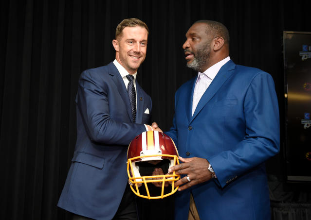 FILE - In this March 15, 2018, file photo, newly signed Washington Redskins quarterback Alex Smith, left, shakes hands and poses with Doug Williams, the NFL football team's senior vice president of player personnel, during a news conference in Ashburn, Va. Acquiring Alex Smith filled a long-term need at quarterback the Redskins didnt think Kirk Cousins was the right fit for. Its not a great sign that Cousins led the Redskins in rushing touchdowns. So before introducing Smith, Williams glanced at him and said: I promise you, we'll get the running back situation straight. (AP Photo/Nick Wass, File)