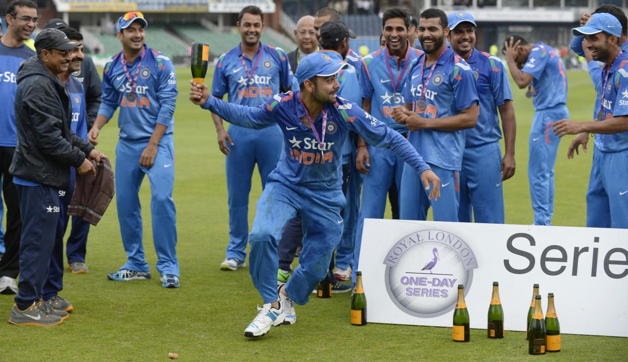 India's Virat Kohli (C) runs with a champagne bottle as the team celebrates winning their one-day cricket series against England at Headingley cricket ground in Leeds September 5, 2014. REUTERS/Philip Brown (BRITAIN - Tags: SPORT CRICKET)