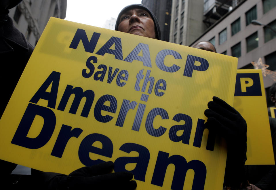 Mary Collie of the NAACP listens to a speaker at a rally calling for an end to predatory lending practices and home foreclosures outside the New York Stock Exchange December 10, 2007.  REUTERS/Jeff Zelevansky (UNITED STATES)