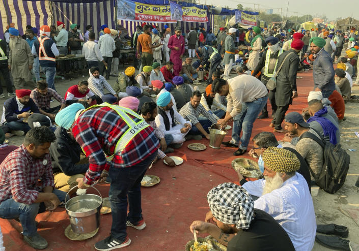 Indian farmers protesting new agriculture eat lunch during a blockade at the Delhi-Haryana state border, Monday, Nov. 30, 2020. Indian Prime Minister Narendra Modi tried to placate thousands of farmers protesting new agriculture laws Monday and said they were being misled by opposition parties and that his government would resolve all their concerns. (AP Photo/Rishi Lekhi)