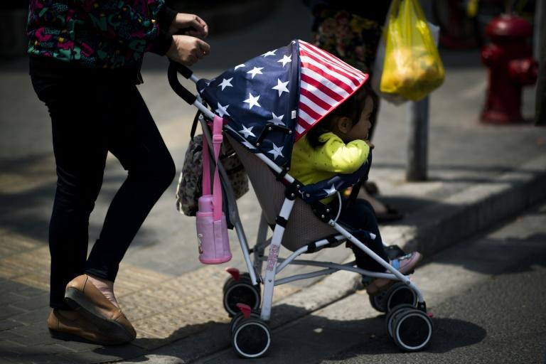 File picture of a woman pushing a child in a stroller, adorned with colours of the US national flag, along a street in Shanghai