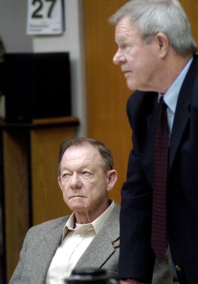 FILE  - This Oct. 27, 2004 file photo shows Jack Lee Harelson, left, in Jackson County Circuit Court in Medford, Ore., with attorney Bob Abel. Authorities said Harelson, a  former insurance agent and amateur archaeologist convicted of looting ancient Indian graves in the Nevada desert and later offering $10,000 in opals for a hit man to kill a former business partner, died Dec. 14, 2012 at the Oregon State Penitentiary in Salem, Ore. (AP Photo/Roy Musitelli, Pool, File)