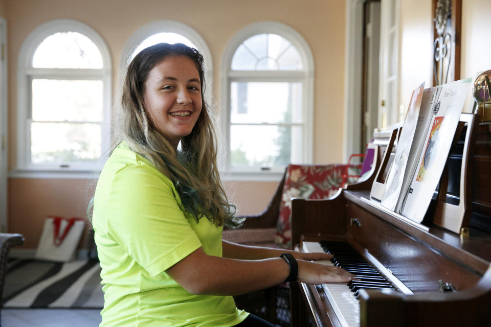 "Grace Brown, 14, poses for a portrait by the piano at her home in Alexandria, Va., Friday, Nov. 1, 2019. Brown chose to take ""online PE,"" utilizing a fitness tracker, so that she could participate in a piano lab as an extra elective. (AP Photo/Jacquelyn Martin)"