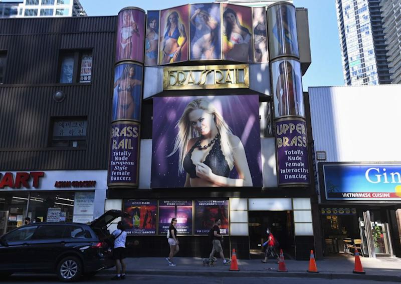 People walk past the Brass Rail strip club in Toronto, on Friday, Aug. 14, 2020. Health officials have warned that as many as 550 people may have been exposed to COVID-19 after an employee tested postivie. (Nathan Denette/The Canadian Press via AP)