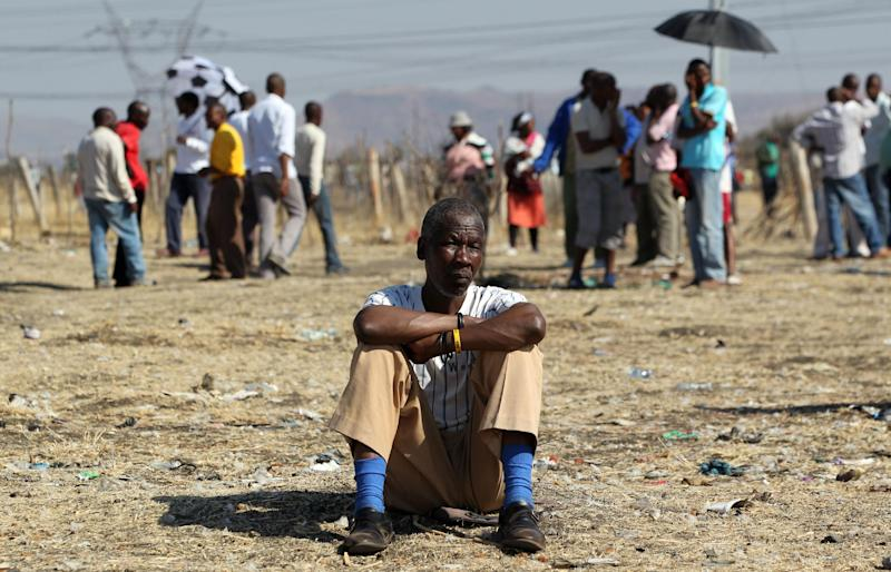 A mine worker Thabo Leribe sits as they wait for a report back from their union at the Lonmin mine near Rustenburg, South Africa, Tuesday, Aug. 21, 2012. Mine workers trickled in Tuesday at the Lonmin platinum mine where 44-people have died in a wildcat strike, as South Africa urged the company to suspend an ultimatum to return to work. (AP Photo/Themba Hadebe)