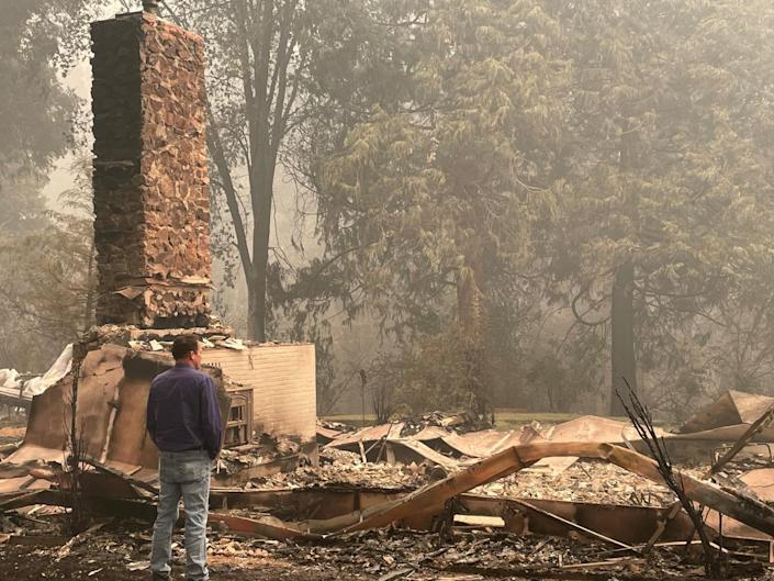 A man looks at the remains of a home incinerated in the Dixie fire.