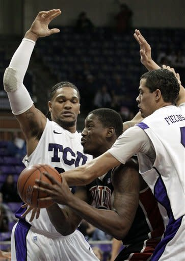 UNLV forward Quintrell Thomas, center, is stopped on his way to the basket by TCU 's Adrick McKinney, left, and Amric Fields (4) in the first half of an NCAA college basketball game Tuesday, Feb. 14, 2012, in Fort Worth, Texas. (AP Photo/Tony Gutierrez)