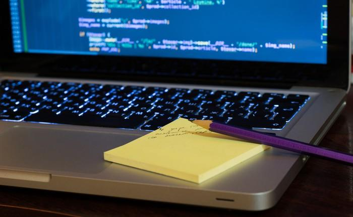 An open laptop with what looks like computer language shown on its screen, and yellow Post-It notes and a purple pencil sitting on the keyboard.
