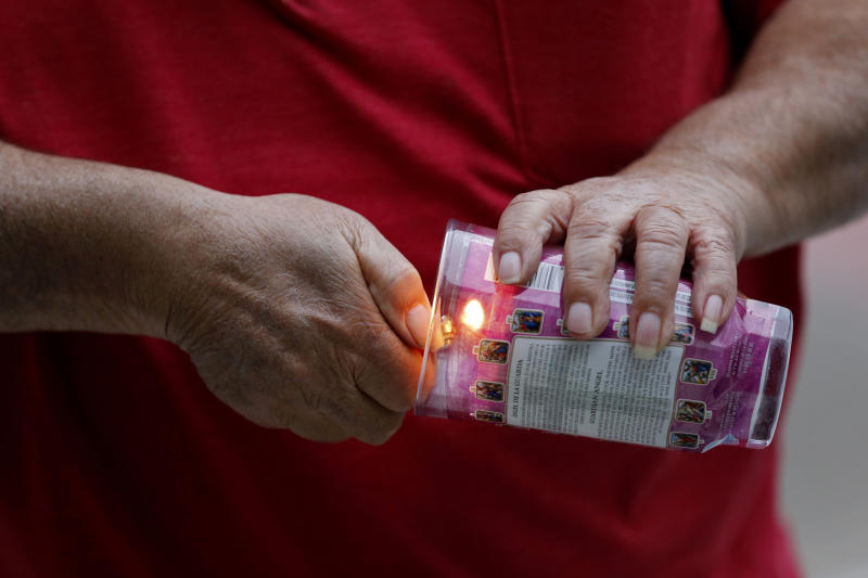 A person lights a candle during a candlelight vigil outside city hall for deceased and injured workers from the Hard Rock Hotel construction collapse Sat., Oct. 12, in New Orleans, on Thursday, Oct. 17, 2019. The vigil was organized by various area labor groups. (AP Photo/Gerald Herbert)