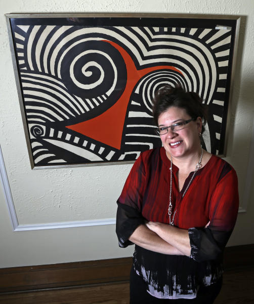 In this Wednesday, Nov. 28, 2012 photo, Karen Mallet stands in front of her Alexander Calder print in her Shorewood, Wis., home. Mallet bought the print for $12.34 at a Goodwill thrift store in Milwaukee. It turned out to be a lithograph by the American artist Alexander Calder worth $9,000. (AP Photo/Morry Gash)