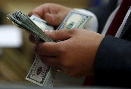 FILE PHOTO: An employee counts U.S. dollar notes in a bank in Cairo