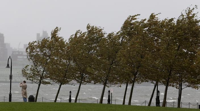 A person takes a photograph of the Hudson River as gusty winds bend trees, Monday, Oct. 29, 2012, in Hoboken, N.J. Hurricane Sandy continued on its path Monday, as the storm forced the shutdown of mass transit, schools and financial markets, sending coastal residents fleeing, and threatening a dangerous mix of high winds and soaking rain. (AP Photo/Julio Cortez)
