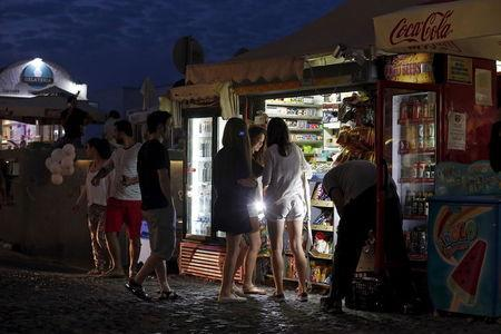 Tourists buy water from a vendor on the Greek island of Santorini, Greece, July 1, 2015. REUTERS/Cathal McNaughton