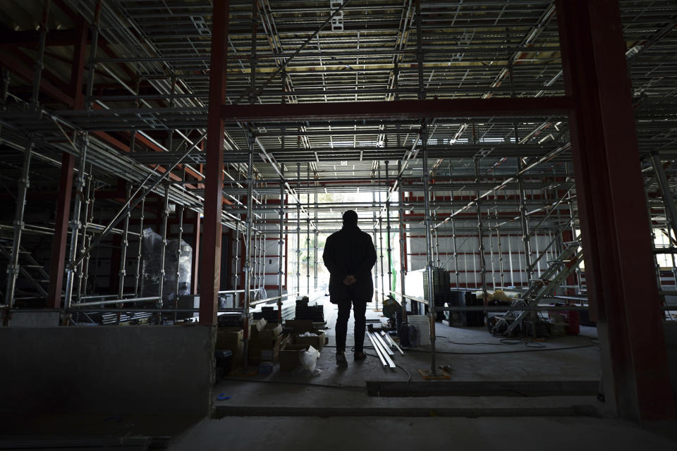 Michihiro Kono, president of Yagisawa Shoten Co., stands at a his factory under construction Friday, March 5, 2021, in Rikuzentakata, Iwate Prefecture, northern Japan. Just a month after a tsunami as high as 17 meters (55 feet) smashed into the city of Rikuzentakata, soy sauce maker Kono inherited his family's two-century-old business from his father. Later this year the ninth generation owner of Yagisawa Shoten Co. will open a new factory on the same ground where his family started making soy sauce in 1807. (AP Photo/Eugene Hoshiko)