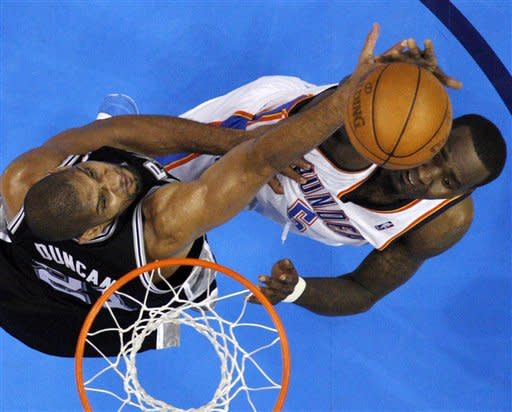 Oklahoma City Thunder center Kendrick Perkins (5) is defended by San Antonio Spurs center Tim Duncan (21) during the first half of Game 3 in their NBA basketball Western Conference finals playoff series, Thursday, May 31, 2012, in Oklahoma City. (AP Photo/Sue Ogrocki)