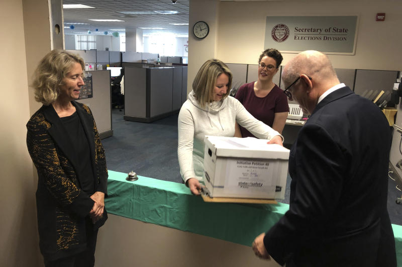 Lydia Plukchi of the Oregon Secretary of State's office in Salem, Ore., accepts on Wednesday, Sept. 18, 2019, a box containing 2,000 signatures backing a proposed ballot measure that would create the most comprehensive law in America requiring the safe storage of weapons, as worker Amanda Kessel, behind her, looks on. Delivering the box are Henry Wessinger, president of the State of Safety Action which is backing the proposed measure, and Rep. Alissa Keny-Guyer. (AP Photo/Andrew Selsky)