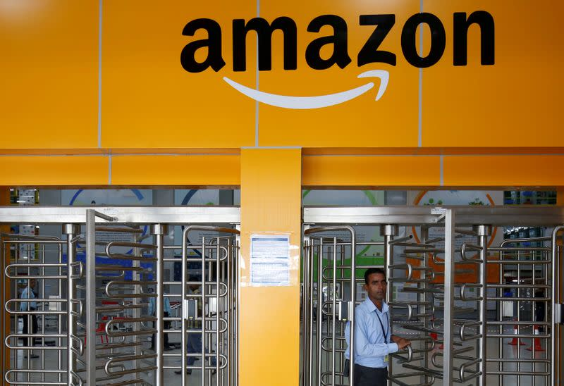 FILE PHOTO: An employee of Amazon walks through a turnstile gate inside an Amazon Fulfillment Centre (BLR7) on the outskirts of Bengaluru