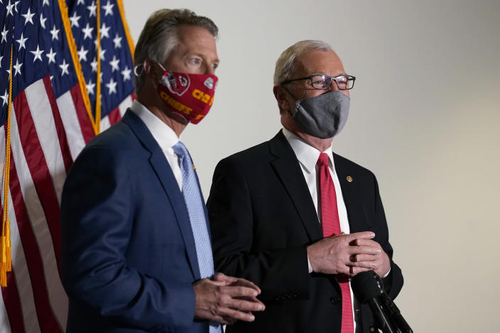 Sen. Roger Marshall, R-Kan., and Sen. Kevin Cramer, R-N.D., talk with reporters before a Republican policy luncheon on Capitol Hill in Washington, Tuesday, Jan. 26, 2021. (AP Photo/Susan Walsh)