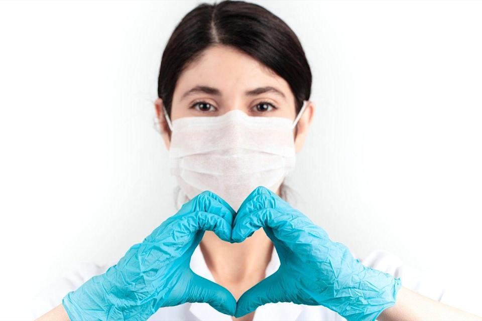 medicine doctor wearing face mask and blue scrubs standing corporate in health care work concept