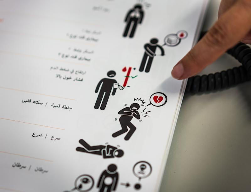 07 August 2019, Hessen, Offenbach: Internist Matthias Zimmer (37) explains in a treatment room at the Ketteler Hospital the use of a booklet showing illustrations and words for complaints in Arabic. The Malteser Hilfsdienst offers medical treatment for people without health insurance once a week, anonymously if desired. Photo: Frank Rumpenhorst/dpa (Photo by Frank Rumpenhorst/picture alliance via Getty Images)