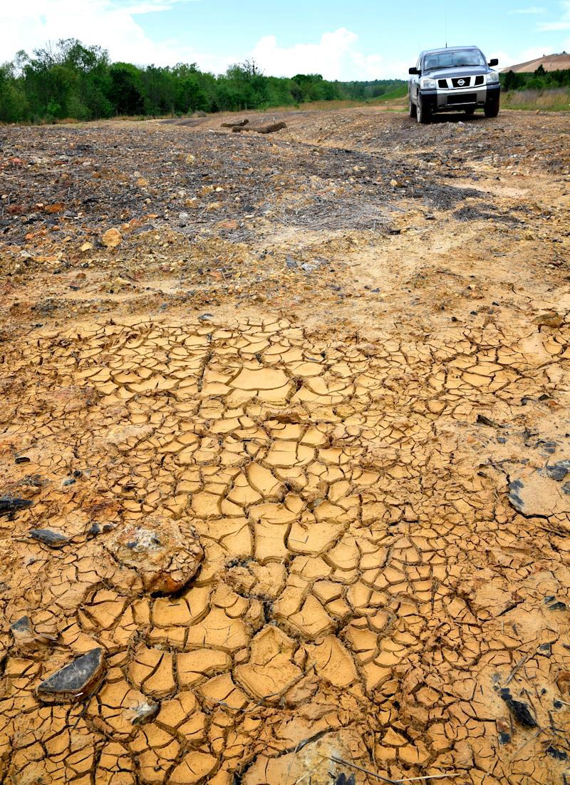 Soil cracks where runoff from the county landfill is