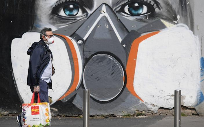 A man walks past coronavirus artwork in Milan - Reuters