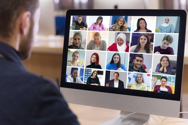 Man looking at screen of video call with numerous others on screen