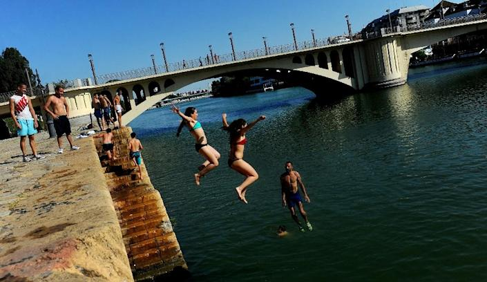 People jump into the Guadalquivir river during a heatwave in Sevilla on June 28, 2015 (AFP Photo/Cristina Quicler)