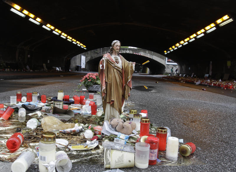 FILE - In This Aug. 23, 2010 file photo candles sit near the site where 21 people died and some 500 were injured in a stampede during the Love Parade in Duisburg, western Germany. German judges have ruled that 10 people indicted over a deadly mass panic at the Love Parade techno music festival in 2010 must stand trial, overturning a lower court's decision. (AP Photo/Frank Augstein)