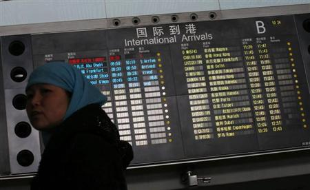 A woman looks back in front of a flight information board displaying the Scheduled Time of Arrival (STA) of Malaysia Airlines flight MH370 (top, in red) at the Beijing Capital International Airport in Beijing, March 8, 2014. REUTERS/Kim Kyung-Hoon/Files