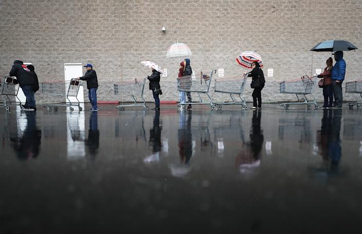 Shoppers wait in line in the rain to enter a Costco Wholesale store on March 14 in Glendale, California.