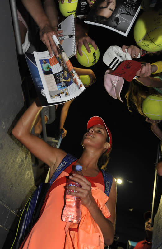 Ana Ivanovic of Serbia signs autographs for supporters after victory in her first round women's singles match against Lourdes Dominguez-Lino of Spain on the second day of the Australian Open tennis tournament in Melbourne on January 17, 2012. Ivanovic won 6-0. 6-3. .   (Photo by Torsten Blackwood Image Strictly Restricted To Editorial Use Strictly No Commercial Use/AFP/Getty Images)