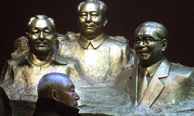 A man walks past busts of Deng Xiaoping, Mao Zedong Jiang Zemin