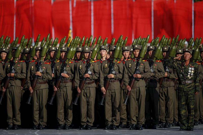Soldiers carry rocket launchers in front of a stand with North Korean leader Kim Jong Un and other officials during the parade celebrating the 70th anniversary of the founding of the ruling Workers' Party of Korea, in Pyongyang October 10, 2015. Isolated
