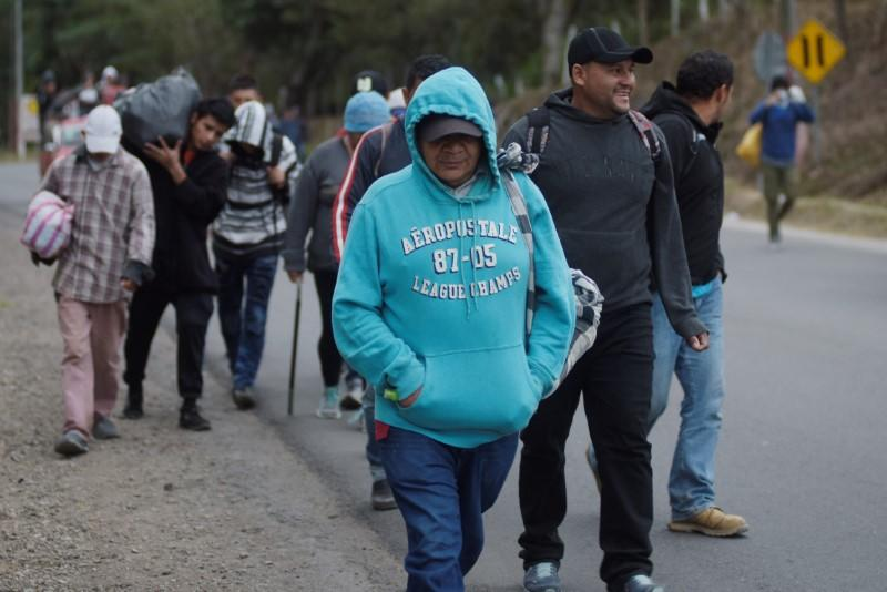 People, part of a caravan of migrants heading toward the United States, walk along a road in Agua Caliente
