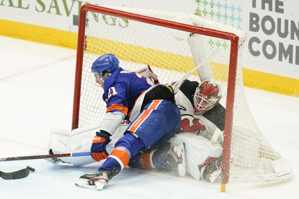 New York Islanders' Kyle Palmieri (21) crashes into New Jersey Devils goaltender Mackenzie Blackwood (29) while scoring a goal during the third period of an NHL hockey game Saturday, May 8, 2021, in Uniondale, N.Y. The Islanders won 5-1. (AP Photo/Frank Franklin II)