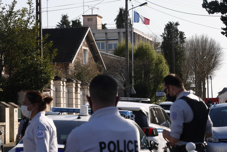 French Police officers stand next to the Police station in Rambouillet, south west of Paris, Friday, April 23, 2021. A French police officer was stabbed to death inside her police station Friday near the famed historic Rambouillet chateau, and her attacker was shot and killed by officers at the scene, authorities said. The identity and the motive of the assailant were not immediately clear, a national police spokesperson told The Associated Press. The police officer was a 49-year-old administrative employee in the station, the spokesperson said. (AP Photo/Michel Euler)