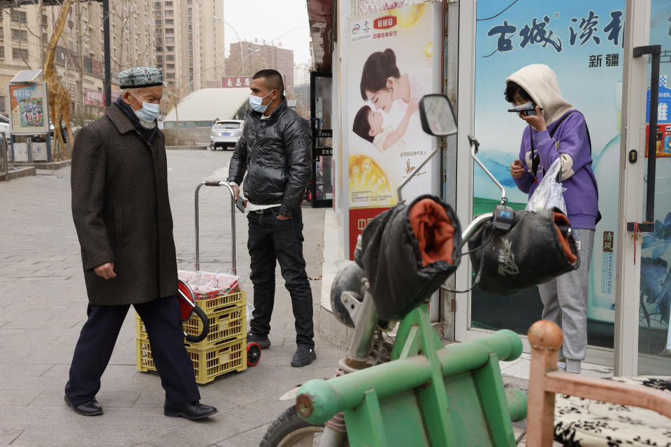 FILE - In this March 18, 2021, file photo, residents wearing masks walk along the streets of Aksu in western China's Xinjiang region. A human rights group appealed to the United Nations on Monday, April 19, 2021, to investigate allegations China's government is committing crimes against humanity in the Xinjiang region. (AP Photo/Ng Han Guan, File)