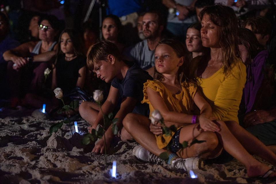 People attend a community vigil on the beach for those missing after the collapse of the Champlain Towers South condominium building in Surfside, Florida on June 28, 2021. (Giorgio Viera/AFP)