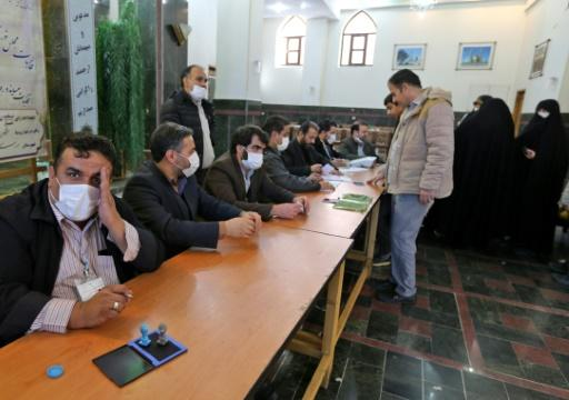 Organisers wear masks as they oversee voting in Iran's Friday parliamentary election days after the coronavirus outbreak first emerged