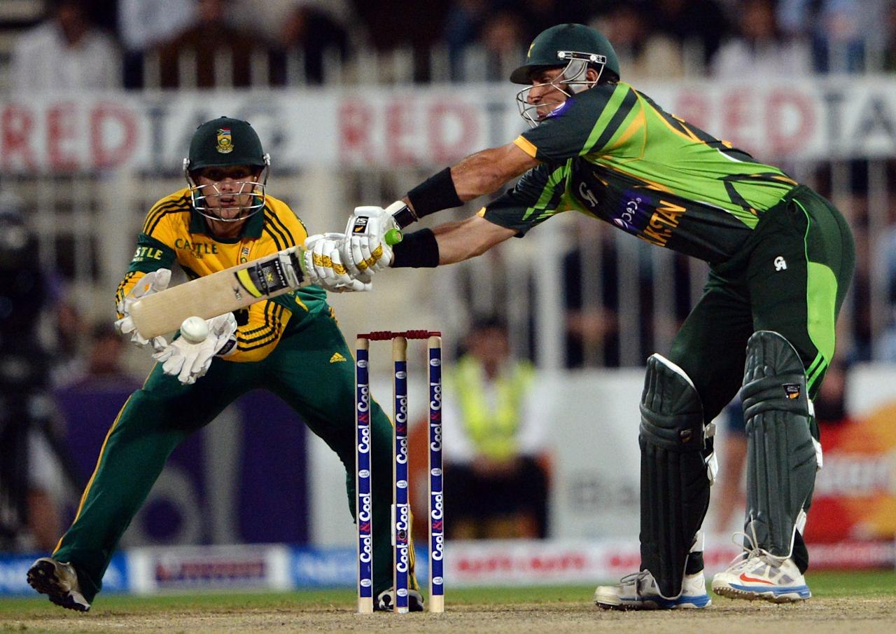 Pakistan's captain Misbah-ul Haq (R) plays a shot as South African wicke keeper Quinton de Kock looks on during the fifth and final day international at Sharjah Cricket Stadium in Sharjah on November 11, 2013. Pakistan were chasing a challenging 268-run target after South African skipper AB de Villiers samshed a 102-ball 115 not out in his team's 268-7 run total. South Africa lead the five-match series 3-1.AFP PHOTO/ASIF HASSAN        (Photo credit should read ASIF HASSAN/AFP/Getty Images)