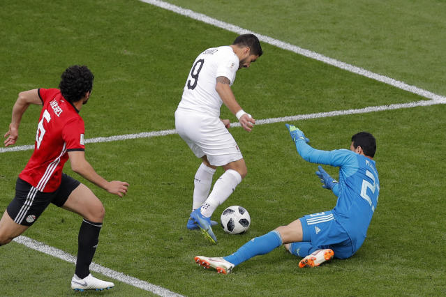 Egypt goalkeeper Mohamed Elshenawy, right, blocks a shot by Uruguay's Luis Suarez, center, during the group A match between Egypt and Uruguay at the 2018 soccer World Cup in the Yekaterinburg Arena in Yekaterinburg, Russia, Friday, June 15, 2018. (AP Photo/Vadim Ghirda)