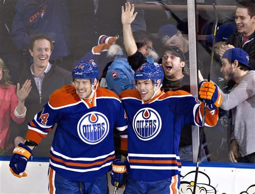 As fans, background, react, Edmonton Oilers' Corey Potter, left, and Taylor Hall celebrate Hall's goal against the Vancouver Canucks during first-period NHL hockey game action in Edmonton, Alberta, Saturday, March 30, 2013. (AP Photo/The Canadian Press, Jason Franson)