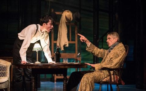 Jeremy Irons gestures cantankerously at a young man - Credit: Wyndham's Theatre