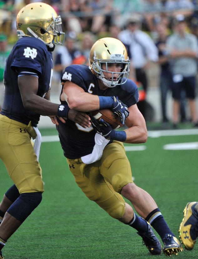 Notre Dame quarterback Everett Golson, left, hands off to running back Cam McDaniel during an NCAA college football game against Rice in South Bend, Ind., Saturday, Aug. 30, 2014. (AP Photo/Joe Raymond)